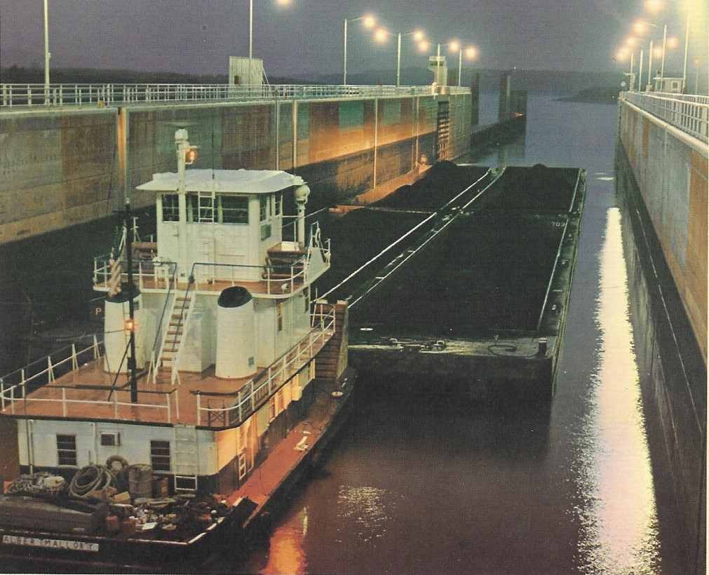Tow vessel traversing lock with barges
